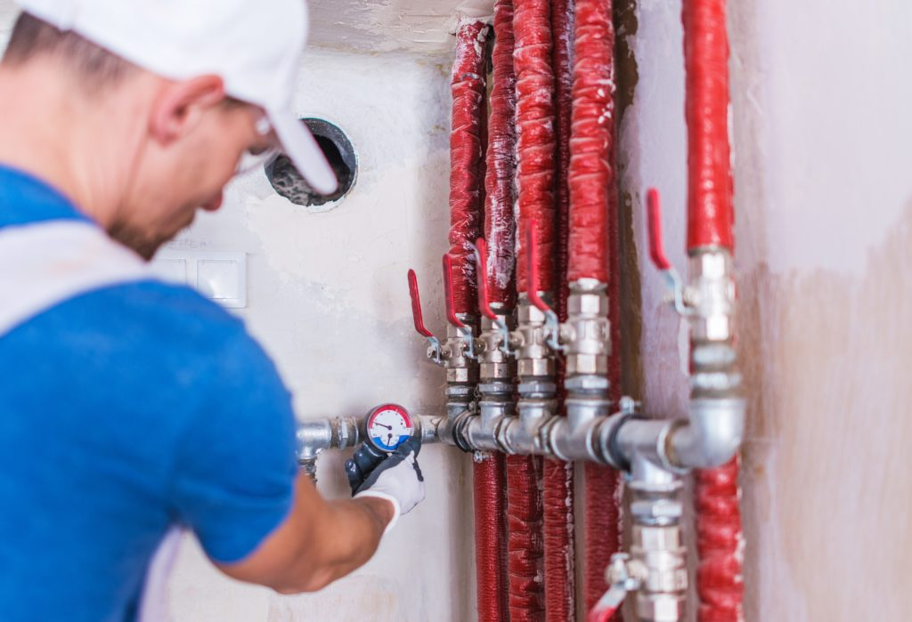 picture of plumber checking pipe pressure with a pressure gauge - essential plumbing tools