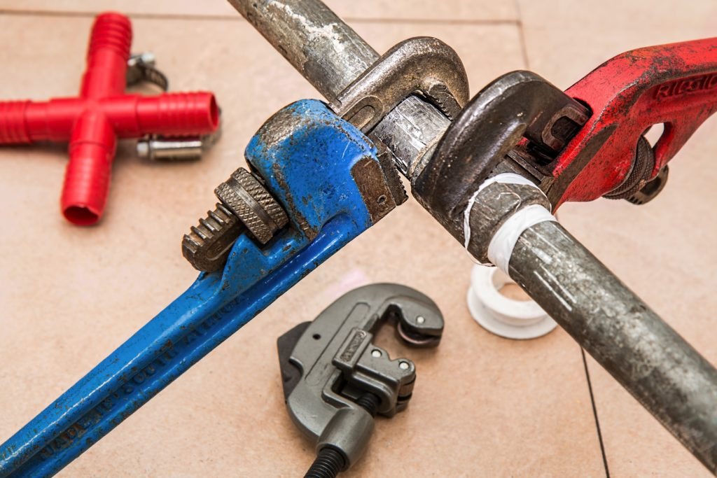 two pipe wrenches fixing a pipe - essential plumbing tools